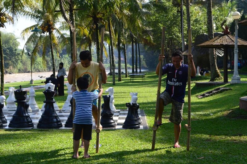 Ayah dan anak yang asyik bermain enggrang