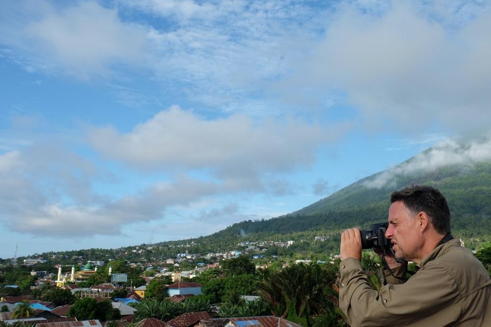 Turis asing yang memotret gunung di seberang