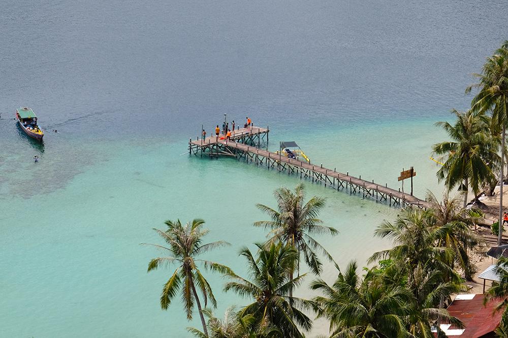 Saya yang masih segar, naik dengan menggebu-gebu. Walaupun peluh akhirnya bercucuran. Tiba di puncak, semua kesusahan terbayar. Pemandangan dari atas bukit sangat indah, Pulau Sikuai terlihat di penghujung, berdekatan dengan daratan antah berantah di Sumatera Barat. Semuanya terlihat hijau. Pepohonan. Lautan. Lalu pirus. Mungkin ada benarnya juga kalau Pulau Pasumpahan disebut-sebut sebagai Raja Ampat-nya Sumatera Barat. Ini adalah versi mininya.